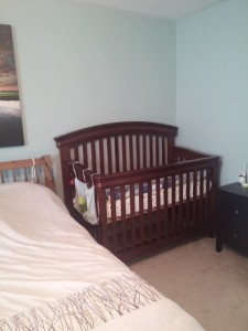 Small nightstand with diapers and sleepers. Crib set up beside the bed.
