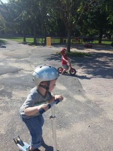 At the park, Liam plays on his scooter with his friend riding his bike in the background